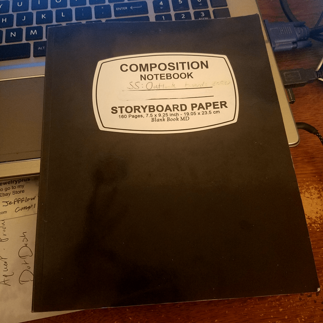 """A photo of a storyboard book on top of a desk and laptop. The book title reads """"Composition Notebook, SS: Outlook Storyboard Paper."""""""
