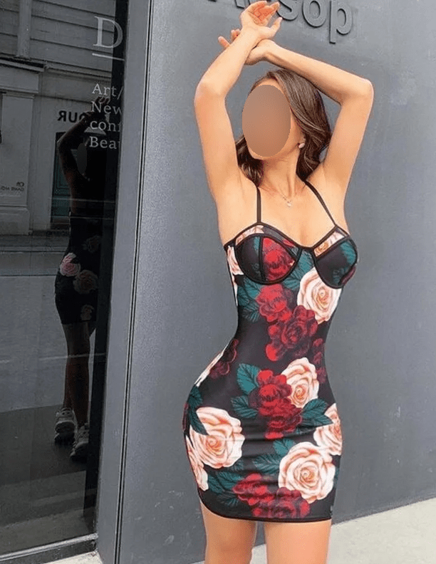 A photograph of a model in a floral dress. A glass window behind her shows that her waist was edited to look skinnier than it actually is.