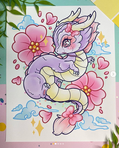 An illustration of a Chinese dragon in front of some flowers and clouds. The illustration is laid on top of a desk. Illustration by Heather.