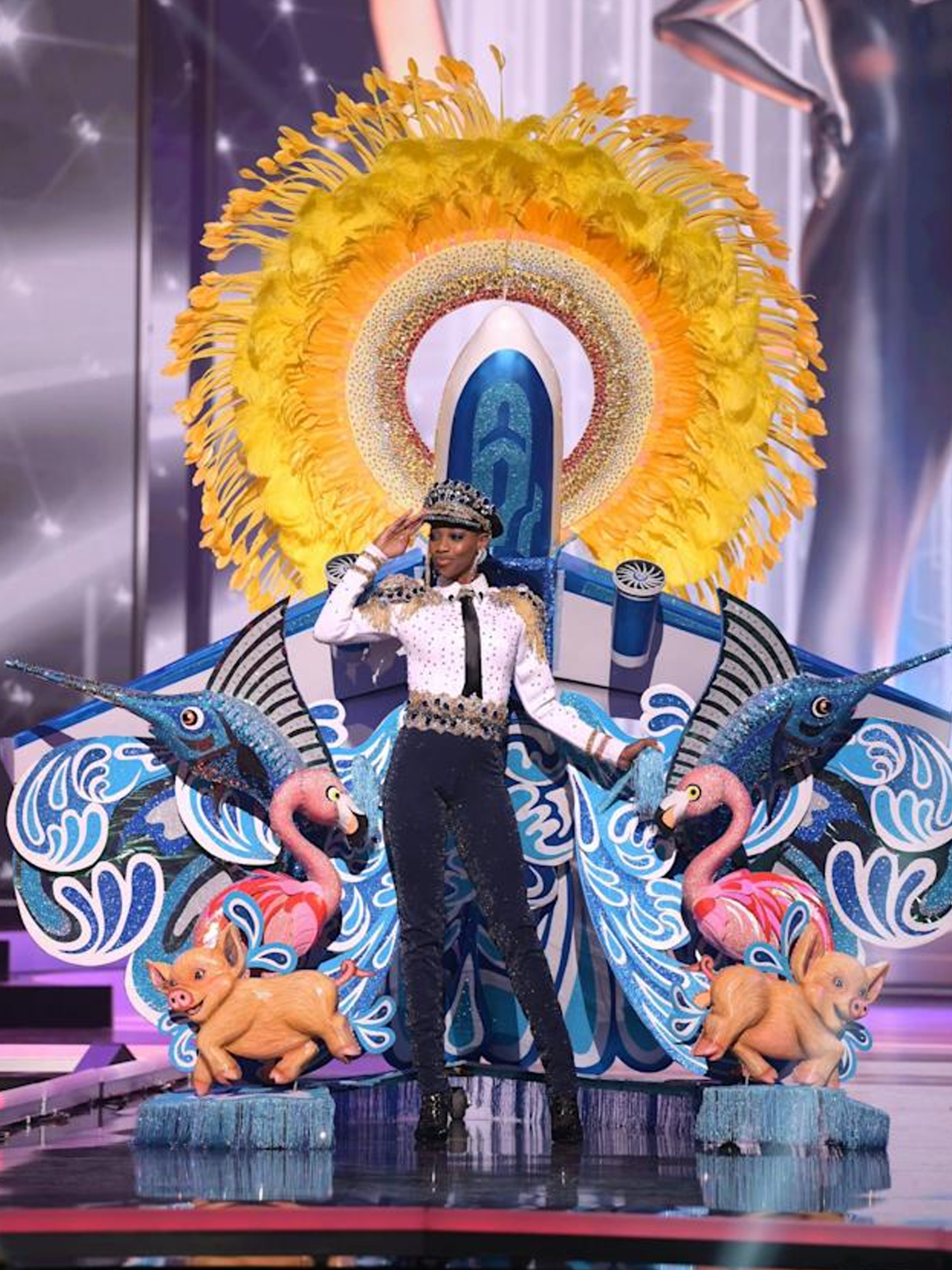 A photograph of the Ms. Universe Bahamas' national 2021 costume. She's wearing a bedazzled pilot uniform, with props of a plane, a sun piece, swordfish, flamingos, and pigs.