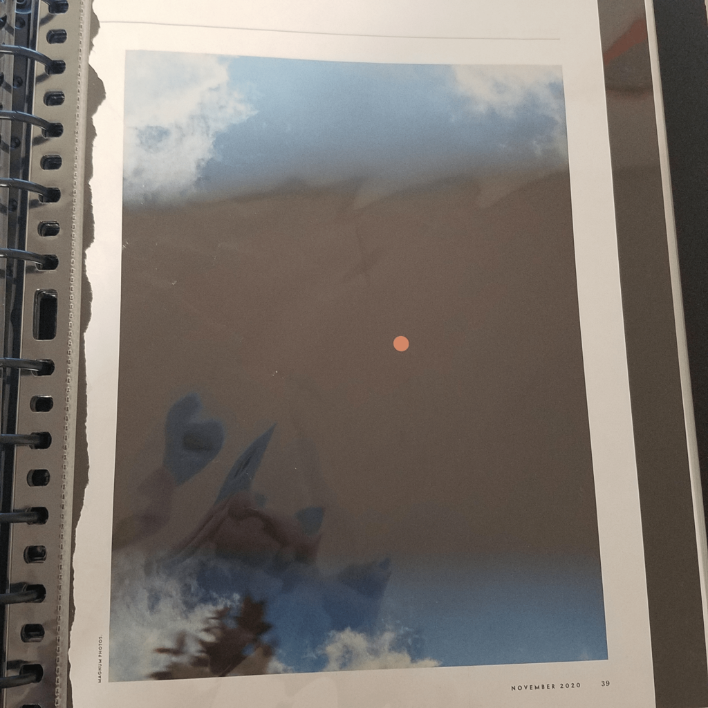 A photo of a magazine page ripped out and put in a binder sleeve. The magazine page is a photograph of a normal, slightly cloudy sky, with a dark, night like streak in the middle and an orange sun inside.